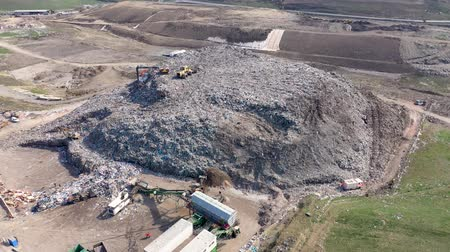 dumping : Aerial top drone view of large garbage pile, trash dump, landfill, waste from household dumping site, excavator machine is working on a mountain garbage. Consumerism and contamination concept