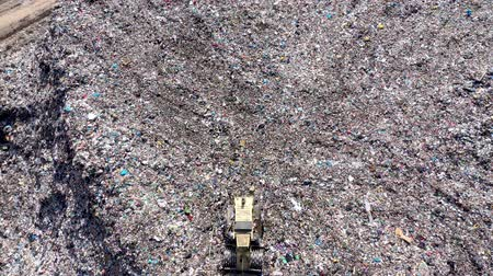 Aerial top drone view of large garbage pile, trash dump, landfill, waste from household dumping site, excavator machine is working on a mountain garbage. Consumerism and contamination concept