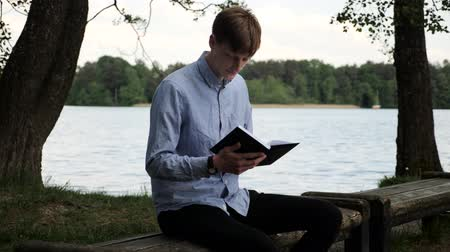 caderno : Attractive student taking notes and work in the park. Young man checking notebook and thinking