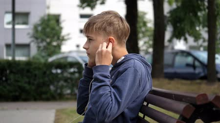 after school : young boy putting on golden earphones, profile, close up shot Stock Footage