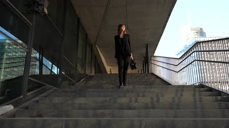 caso : young stylish business woman walking down the stairs, long shot
