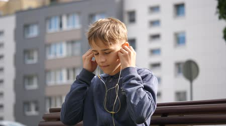 searches : young boy puts headphones on and searches for the song in the smartphone, close up