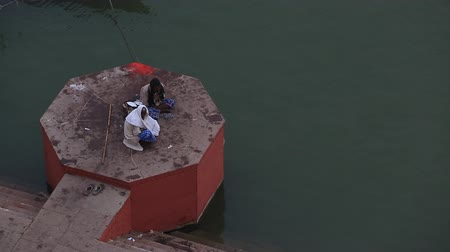 alku : Varanasi, India, November 2015. Two men sitting in a chat room and watch the Ganges River. Stock mozgókép