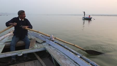 kürek çekme : Varanasi, India, December 2015. A man rowing in a rowboat on the river ganges at sunset. Stok Video