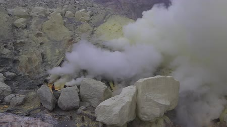 кратер : East Java, Indonesia, February 2016: Un-equipped miners extract sulfur from the Kawah Ijen volcano into a toxic cloud of sulphurous gases.