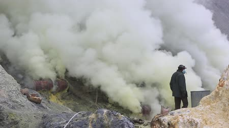 sulfur : East Java, Indonesia, February 2016: Un-equipped miners extract sulfur from the Kawah Ijen volcano into a toxic cloud of sulphurous gases.