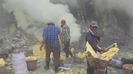 kotel : East Java, Indonesia, February 2016: Un-equipped miners extract sulfur from the Kawah Ijen volcano into a toxic cloud of sulphurous gases.