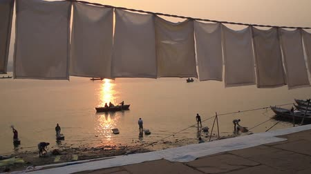 Hanging clothes in an outdoor laundry in a Ganges ghat in Varanasi at sunset.