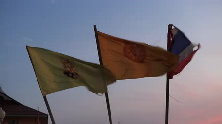 Bangkok, Thailand, March 2016: Buddhist and Thai flags waved at sunset.