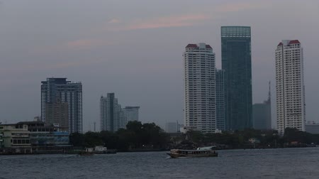 Boats on the Chao Phraya River with skyscrapers in the background at sunset.