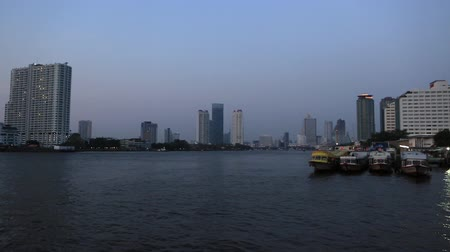 phraya : Bangkok, Thailand, March 2016: Boats on the Chao Phraya River with skyscrapers in the background at sunset.