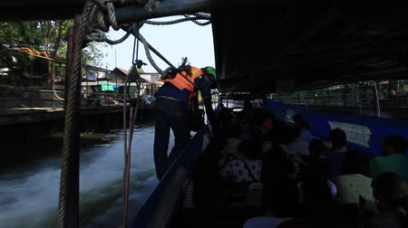 gyűjtő : Bangkok, Thailand, March 2016: Ticket collector in a speedboat on a canal of the Chao Phraya River.