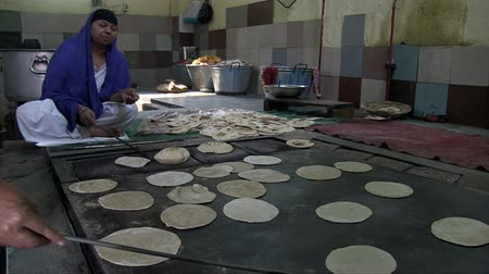 Дели : Old Delhi, India, November 2011: Women cooking Chapati in a Sikh temple in the city. Стоковые видеозаписи