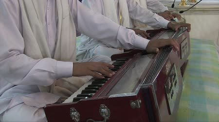 People playing an harmonium at a Sikh temple in the city. Stock mozgókép