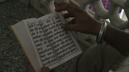 holy book : Old Delhi, India, November 2011: People reading Guru Grant Sahib, the Sikh holy book in a city temple.