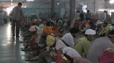 turban : Old Delhi, India, November 2011: People eating in the dining-room at a Sikh temple in the city.