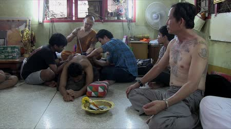 nakhon : Nakhon Chai Si, Thailand, March 2012: Buddhist monk tattooing a man in Wat Bang Phra. Stock Footage