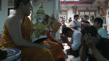 wat : Nakhon Chai Si, Thailand, March 2012: Buddhist monk putting ceremonial masks on the believers in Wat Bang Phra. Stock Footage