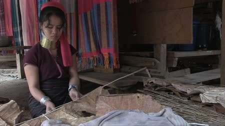 Mae Hong Son, Northern Thailand, March 2012: A woman at work sewing leaves to build the roof of a hut in the Burmese Karen refugee village known for its long-neck women. Stock mozgókép