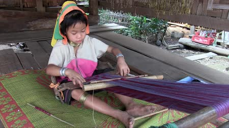 Mae Hong Son, Northern Thailand, March 2012: Girl working on a handloom in the Burmese Karen refugee village known for its long-neck women.