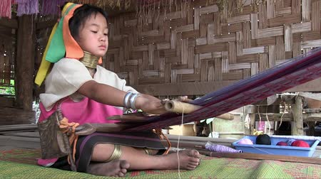 they : Mae Hong Son, Northern Thailand, March 2012: Girl working on a handloom in the Burmese Karen refugee village known for its long-neck women.