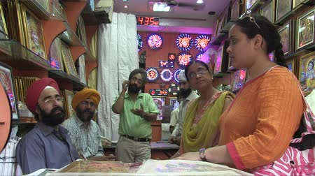 Old Delhi, India, November 2011: Women buying religious objects at a Sikh shop.