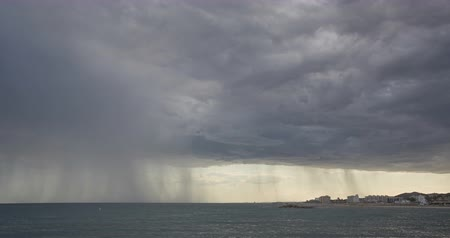 Stormy clouds and heavy rain time lapse on the coast of Tarragona, Spain, during the afternoon.