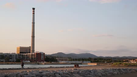 Thermal power coal plant on the coast of Mediterranean Sea, near the beach of Cubelles, Tarragona, Spain, during the afternoon. Stock mozgókép