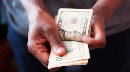 gotówka : Close up of a african american person counting 10 dollars bills