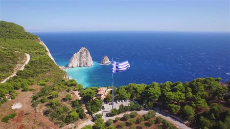 Санторини : 4K aerial view of Greek national flag waving in the sky in Keri in Zakynthos (Zakynthos) island in Greece