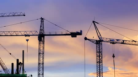 жилье : Construction work at sunset. Tower cranes are used to complete the task quickly.