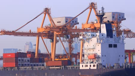 importação : Container Cargo freight ship with working crane bridge in shipyard at evening