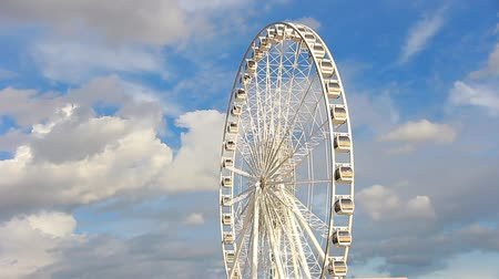 tekerlekler : Ferris wheel has a background sky and clouds.