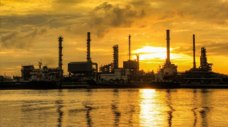 ekonomi : Refining plant on a river with clouds in the evening, time lapse.