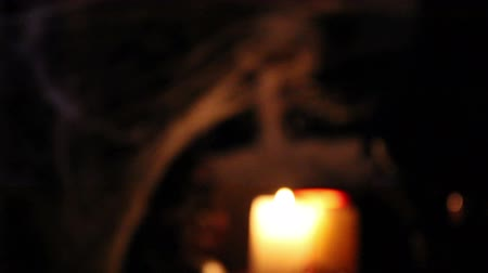 Focus shot of Halloween set up -  skeleton prop with candle in front come into focus.