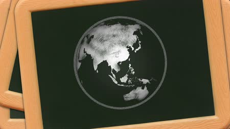 A chalk sketch of the earth rotates on a stack of childrens plastic chalkboards. Loop-able. Wideo