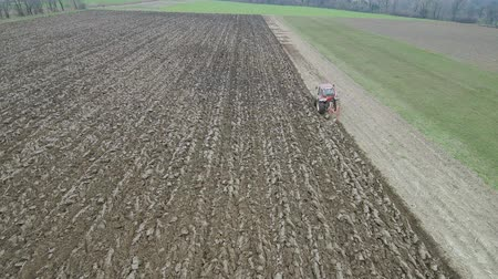 plough land : Agriculture and farming - Tractor plough a field in early spring aerial footage