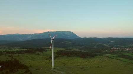 clean electricity production : Aerial - Wind turbine blocking the sun with propeller at sunset Stock Footage