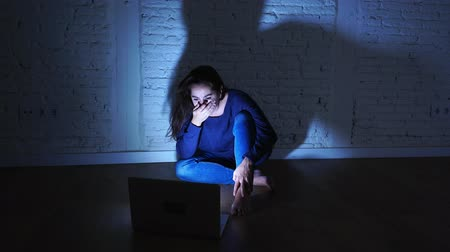 vystavený : Sad and scared female Young woman with computer laptop suffering cyberbullying and harassment being online abused by stalker or gossip feeling desperate and humiliated in cyber bullying concept. Dostupné videozáznamy