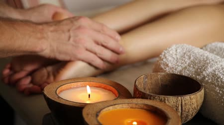 sůl : young woman gets a foot massage in the spa salon. close-up of candles. male hands slide on the female legs Dostupné videozáznamy