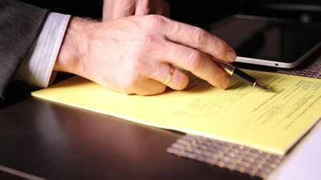 ручки : Businessman sitting office desk signs a bill comparing them, with the pc tablet. close-up hands of a man and a fountain pen