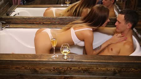 beyaz şarap : young couple drinking foaming champagne and cognac and softly kissing in old bathroom close up Stok Video