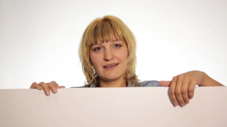 holding : Smiling happy woman standing behind and leaning on a white blank billboard or placard, shows thumb to the top and hiding behind a placard. over white background Stock Footage