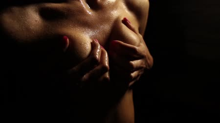 болваны : naked woman stroking her boobs on a dark background. Water droplets on her skin