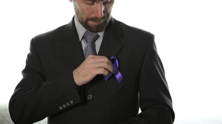 brasão : healthcare and social problems concept - Close-up of man hands holding purple domestic violence and homophobia awareness ribbon