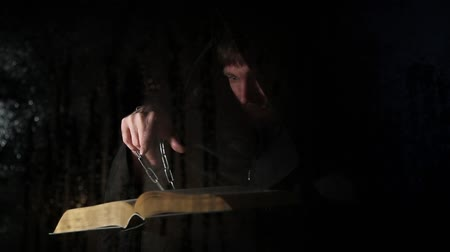 cassock : necromancer casts spells from thick ancient book by candlelight, behind transparent glass covered by water drops on a dark background