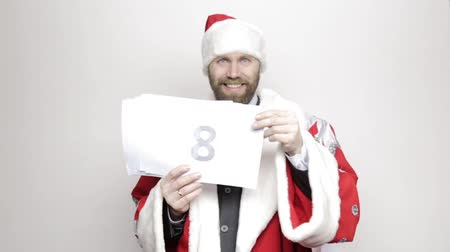 finale : businessman in a suit of Santa Claus holds a sheet of paper with numbers. final countdown Stock Footage