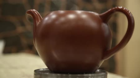 teabag : clay teapot with hot tea on a heated base steaming