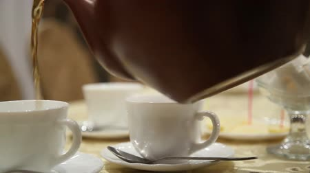 teabag : Pouring tea into cup on table from clay kettle steaming