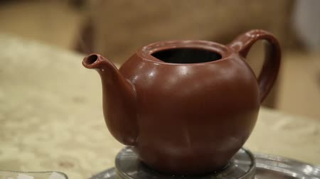 infusão : clay teapot with hot tea on a heated base steaming